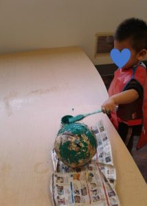 Child paints a big paper mache ball with green paint and a brush.