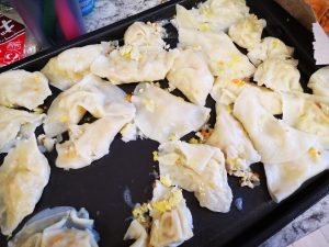 In a tray, cooked dumplings are cooling before being served to the children.