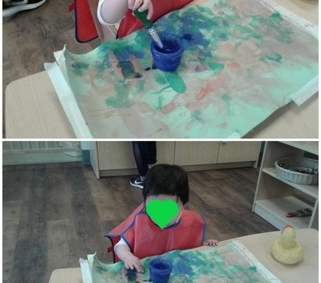 a child paints with watercolours on posters.